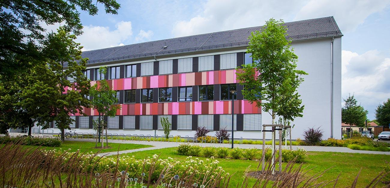Weißes Haus mit einigen in rottönen gehaltenen Panelen, davor eine Freifläche mit Rasen und einigen Bäumen