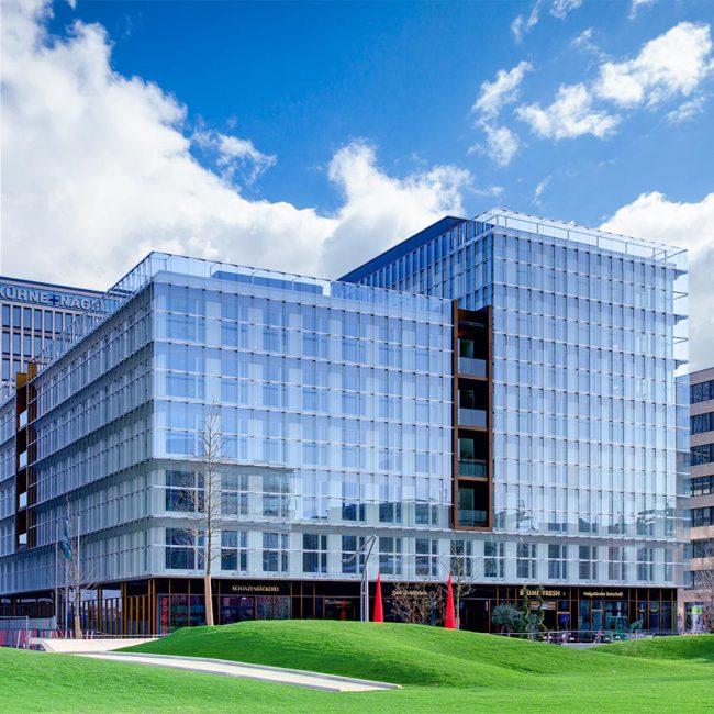 Verglastes Gebäude mit reflexionen des blauen Himmels und eine Rasenanlage davor