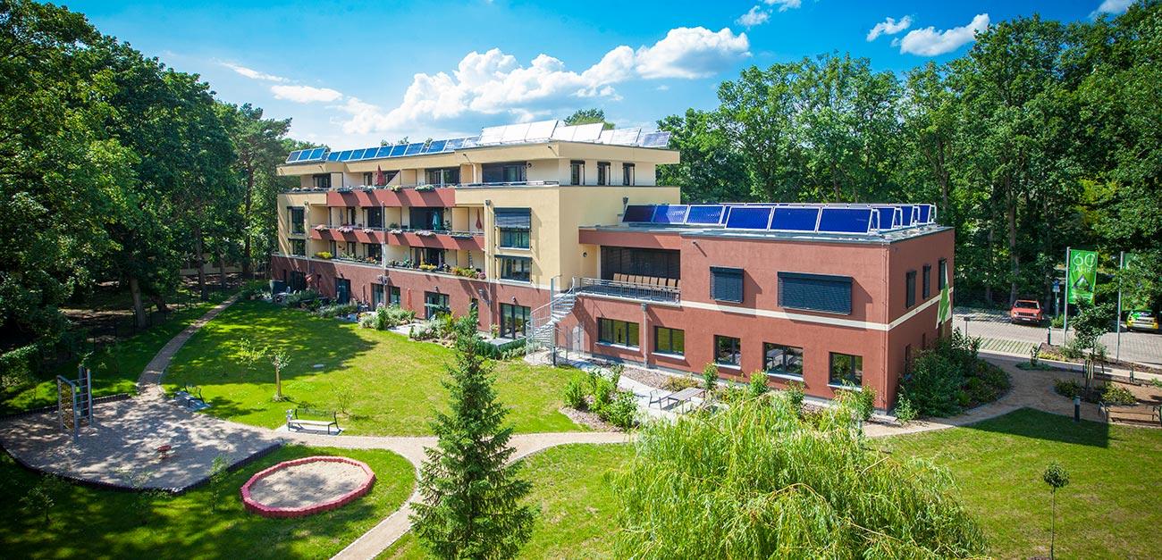 Vogelperspektive vom Sonnenhaus. Rotbraunes Gebäude und grüne Pflanzen und Rasen davor. Auf dem Haus ist eine Solarthermieanlage zu sehen. Im Hintergrund sind Bäume zu sehen