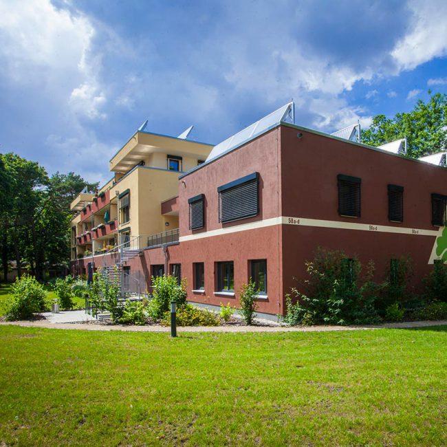 Rotbraunes Gebäude und grüne Pflanzen und Rasen davor. Auf dem Haus ist eine Solarthermieanlage zu sehen.