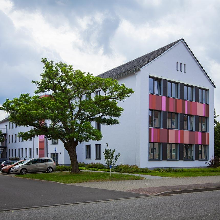 Weißes Haus mit einigen in rottönen gehaltenen Panelen und davor ein Baum und Parkplätze mit Autos