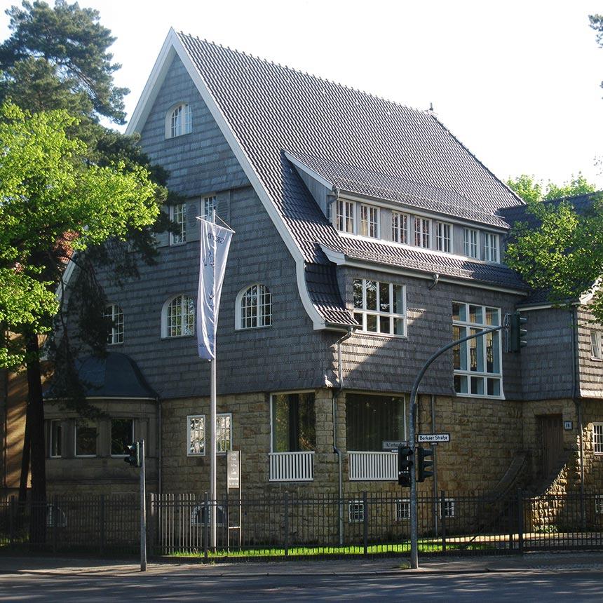 Vierstöckige Villa mit grauen spitz zulaufenden Dach, die Wände sindd aus Naturstein, im Vordergrund ist eine Kreuzung mit Ampel