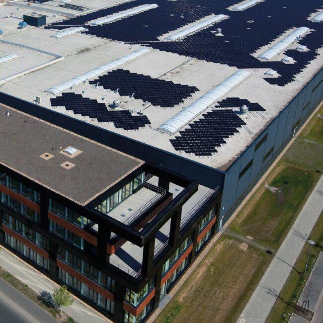 Logistikhalle in Vogelperspektive auf dem Dach ist eine weitflächeige Solaranlage