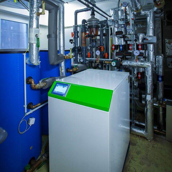 Ansicht einer Geothermieanlage in grau und grün mit vielen Rohren im Hintergrund