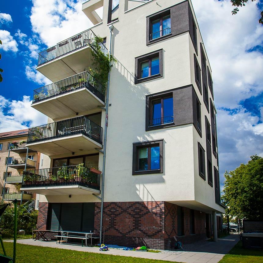 Ansicht eines vierstöckigen Hauses in Beige mit grauen Fenstereinfassungen und je Stockwerk ist ein Balkon zu sehen
