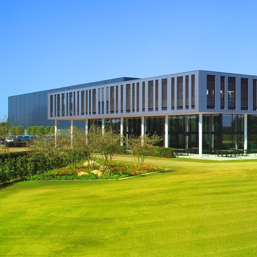 Ein dunkelgraues modern gestaltetes Industriegebäude im vorderen Teil mit großzügigen Fenstern, Davor eine Rasenanlage