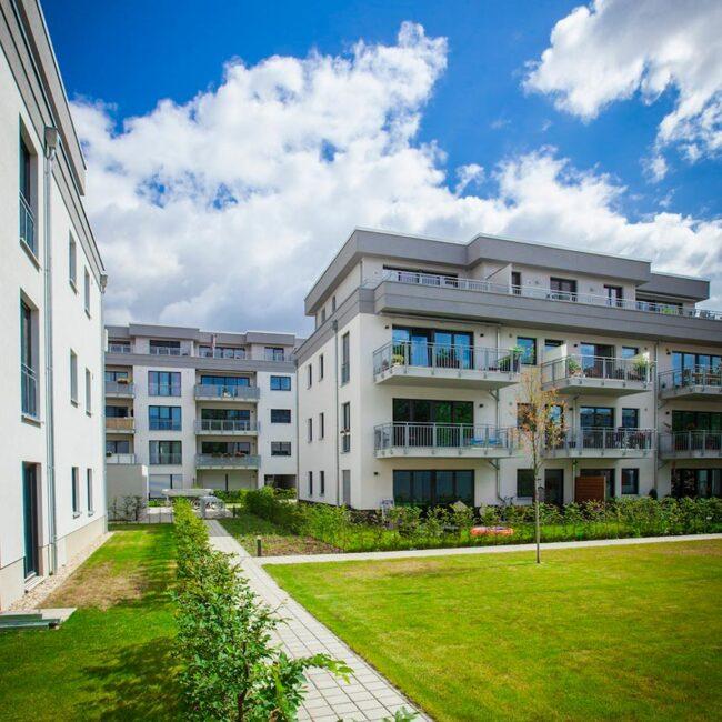 Vierstöckiges Reihenhaus in weiß und grau mit Balkonen davor eine Rasenfläche mit Wegen die von Streuchern eingerahmt sind