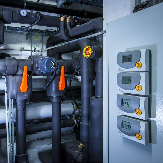 links schwarz verkleidete Heizungsrohre mit orangen Schieberhebeln, rechts ein Schaltschrank mit vier Digitalanzeigen und Bedienungselementen