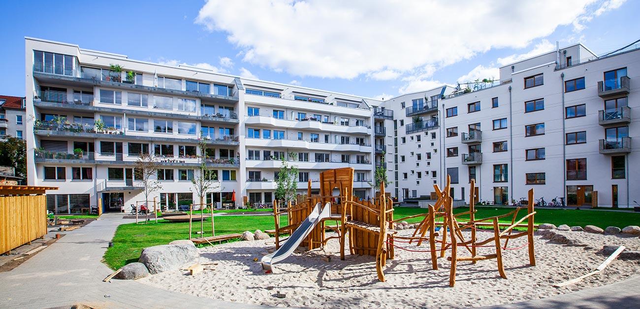 Im Vordergrund ist ein Spielplatz mit einer Kletteranlage aus Holz zu sehen und im Hintergrund ist Reihenhaus in Weiß mit vielen Fenstern und Balkonen zu sehen das den geschaffen Platz umschließt