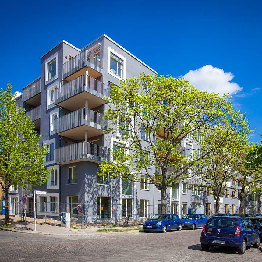 Ein Haus mit grauer Faßade mit Balkonen und Fenstern das an einer Staßenkreuzung einer Nebenstrße steht. Einige Bäume und Autos stehen davor