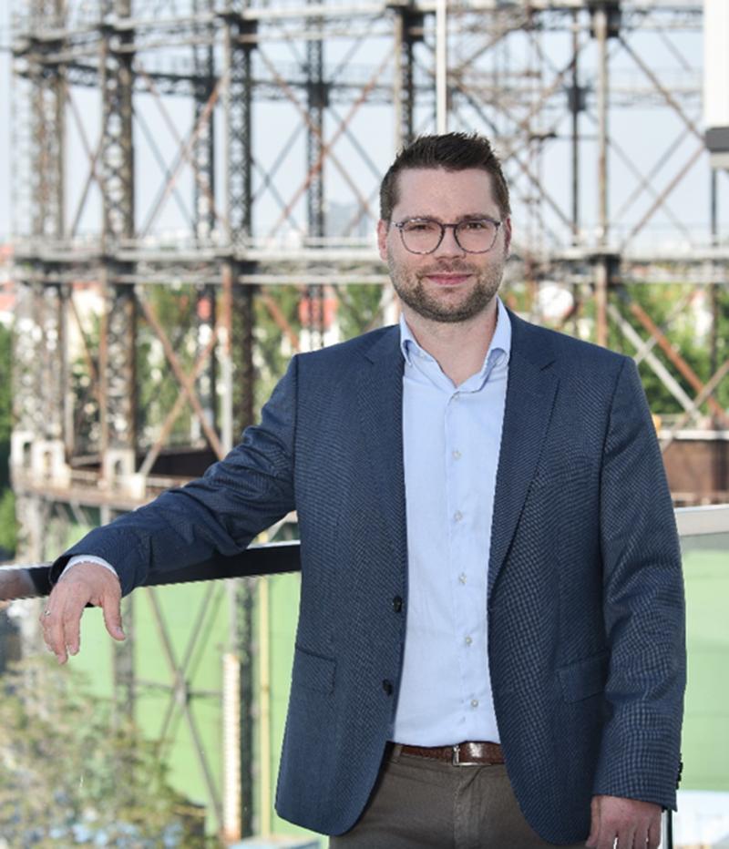 Paul Otto Geschäftsführer Geo-En, junger Mann, mit modernen Bart und Brille, gut gekleidet, lehnt am Geländer im Hintergrund ist das Gasometer zu sehen