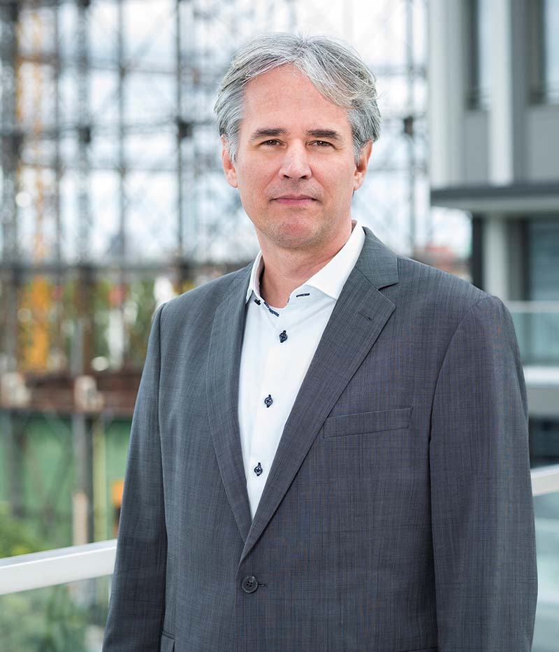 Dr. Alexander Meder, ein gut gekelideter Mann mit grauen Haaren, im Hintergrund ist das Gasometer zu sehen